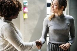 Two women shaking hands. Verksamhetsutvecklare sökes