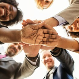 Bygga en stark företagskultur. Människor i en ring som lägger händerna på varandra och ler.